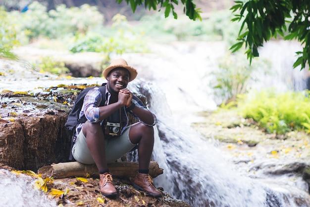 Entspannende freiheit des afrikanischen mann-reisenden am wasserfall