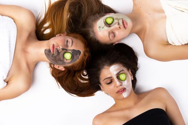 Entspannende freundinnen mit verschiedenen gesichtsmasken und gurkenringen an den augen. hochwertiges foto