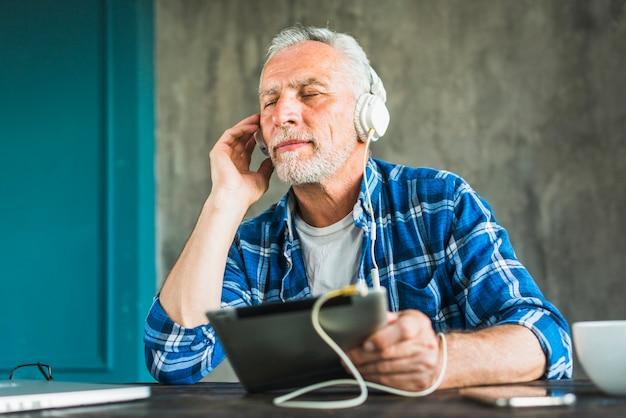 Entspannende hörende musik des älteren mannes auf digitaler tablette