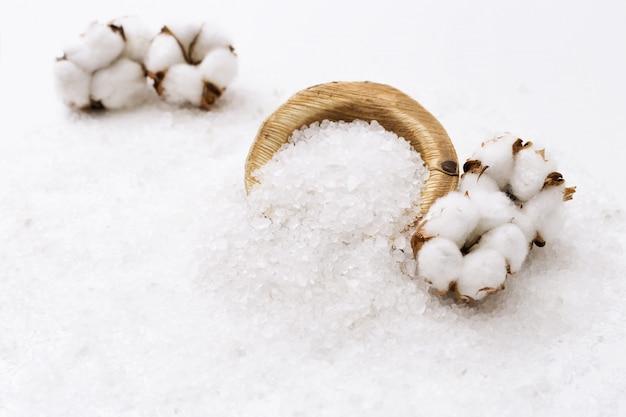 Entspannende kurortzusammensetzung, weißes seesalz und blumen des baumwollabschlusses oben.
