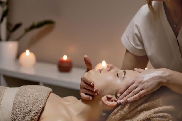 Entspannende massage. frau, die kopfmassage am spa-salon, seitenansicht empfängt.