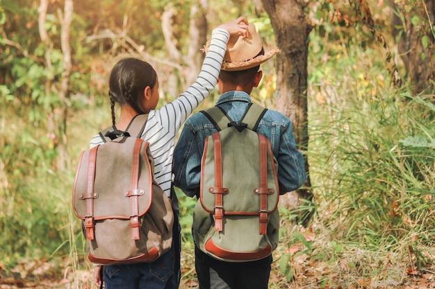 Entspannende momente, asiatische kinder mit hellem rucksack, der in der natur während der ferien genießt.