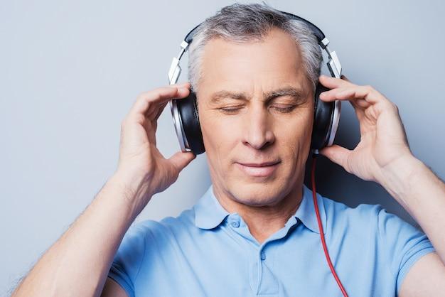 Entspannende musikzeit. porträt eines älteren mannes mit kopfhörern, der musik hört und die augen geschlossen hält, während er vor grauem hintergrund steht