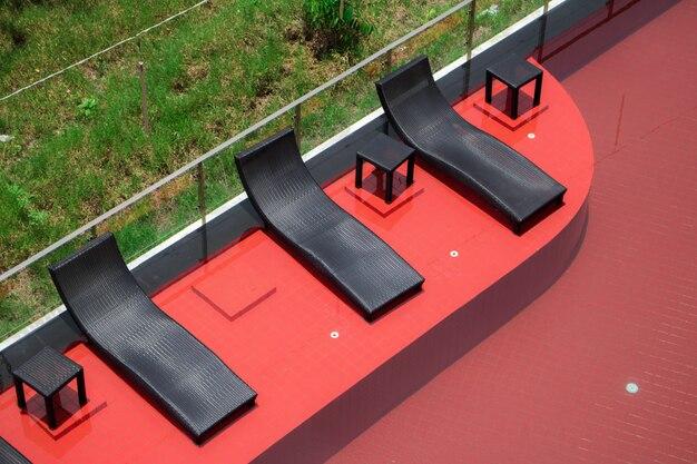 Entspannende schwarze rattanstühle neben swimmingpool