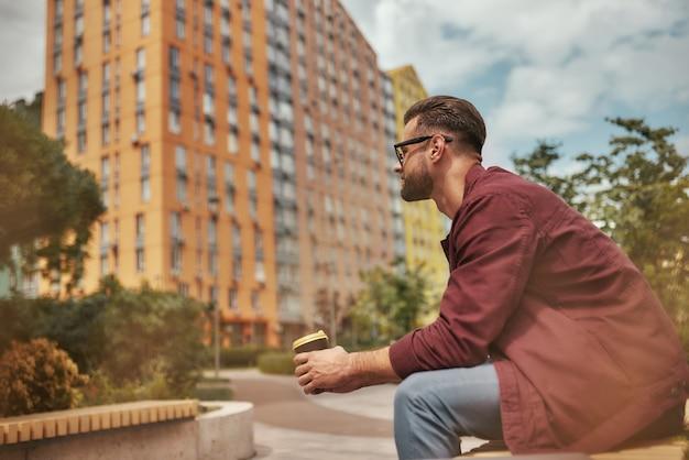 Entspannende seitenansicht eines gutaussehenden mannes mit stoppeln in freizeitkleidung, der im sitzen kaffee trinkt