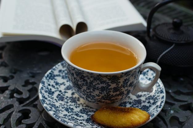 Entspannende teezeit und lesen auf der veranda auf einem eisentisch. welttagbuch