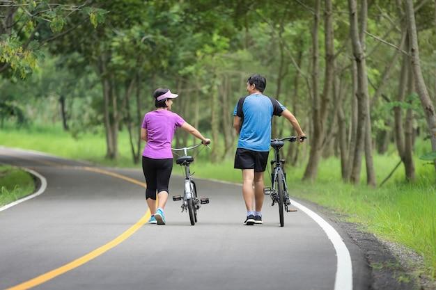 Entspannende übung des paares mittleren alters mit fahrrad im park