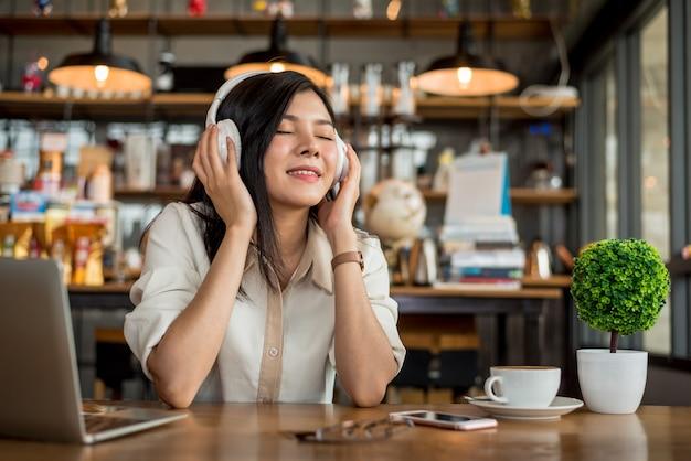 Entspannende und hörende musik der glücklichen asiatin in der kaffeestube mit computerlaptop