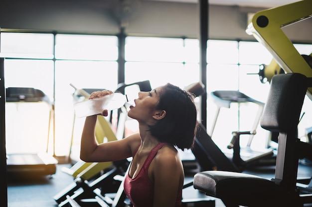 Entspannende und trinkwasser der attraktiven sitzfrau nach training in der turnhalleneignung