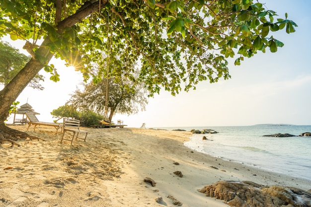 Entspannende zeit der sommerferien auf paradiesstrand mit sonnenlicht durch bäume