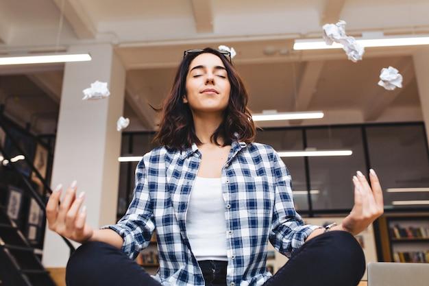 Entspannende zeit freudige junge brünette frau, die meditation auf tisch im büro umgibt fliegende papiere. pause machen, pause, kluger schüler, entspannung, großer erfolg, träumen.