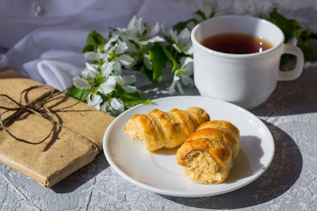 Entspannende zeit und glück mit einer tasse tee mit unter frischen frühlingsblumen. morgentee mit kuchen an einem warmen, sonnigen tag. hübsche geschenkbox mit einfachem braunem bastelpapier umwickelt und mit jute verziert.