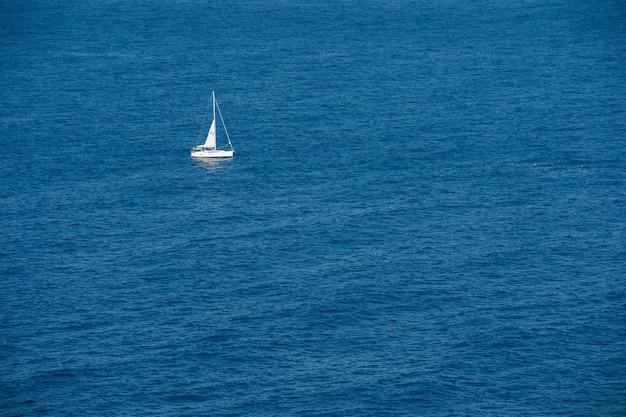 Entspannender blick auf das blaue meer mit einem kleinen weißen segelboot an einem sonnigen tag