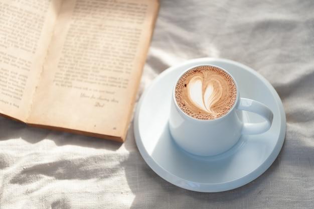 Entspannender feiertagsmorgen mit heißem, herzförmigem latte-art-kaffee in einer weißen kaffeetasse, die mit dem warmen morgensonnenschein aus dem fenster auf das buch gelegt wird, um sich entspannt und entspannt zu fühlen