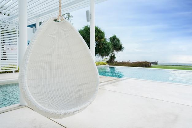 Entspannender hängender stuhl des weißen rattans am swimmingpool auf seeansicht