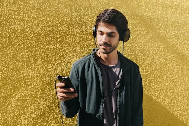 Entspannender junger mann mit telefon