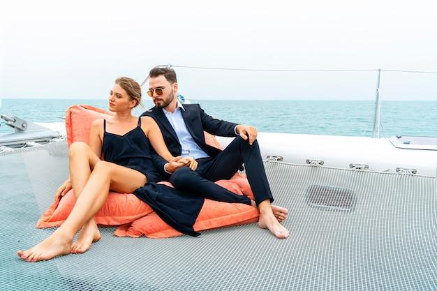Entspannender paarluxusreisender im netten kleid und in der reihe sitzen auf bohnentasche im teil der kreuzfahrtyacht.