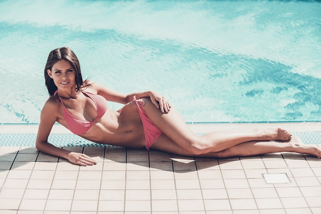 Entspannender pool. in voller länge der schönen jungen frau im bikini, die am pool liegt und lächelt