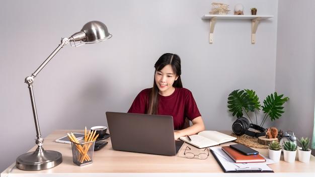 Entspannendes asiatisches geschäftsmädchen benutzt laptop, der fern von zu hause auf dem schreibtisch als freiberufler arbeitet
