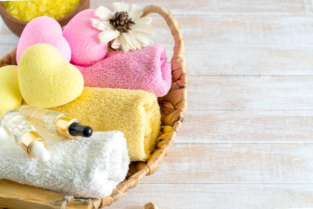 Entspannendes badzubehör mit gelben und rosa herzförmigen badebomben, körperbürste, serum, palo santo, handtüchern und blumen