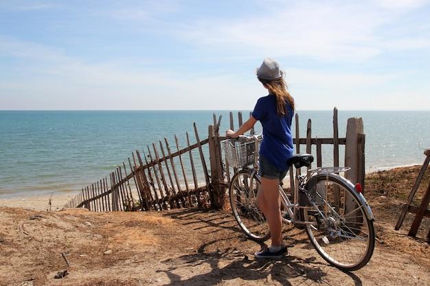 Entspannendes mädchen mit dem fahrrad, das auf dem meer steht