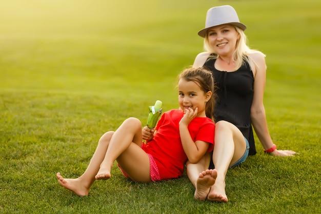 Entspannendes sitzendes gras der schönen jungen muttertochter
