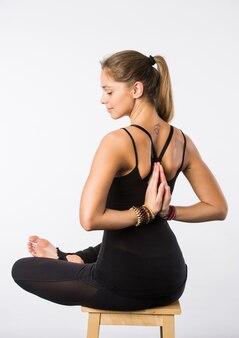 Entspannt fühlen. junge angenehme frau, die im lotussitz auf stuhl mit geschlossenen augen sitzt und ihre handflächen zusammenstellt.