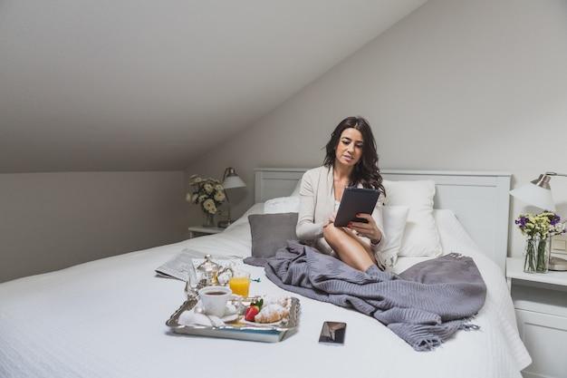 Entspannt junge frau mit tablette in ihrem schlafzimmer