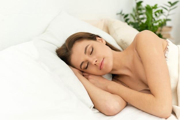 Entspannt lächelnde frau unter weißer bettwäsche im bett im schlafzimmer, die angenehme träume hat, die augen geschlossen hält, volle entspannung zu hause und eine ruhige atmosphäre genießt.