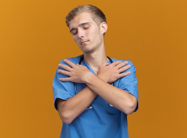 Entspannt mit geschlossenen augen junger männlicher arzt, der arztuniform mit stethoskopkreuzung trägt und hände auf schultern legt, die auf orange wand isoliert sind