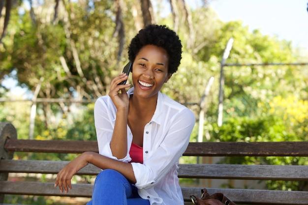 Entspannte afrikanische frau, die auf einer parkbank sitzt und handy verwendet