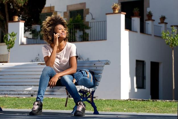 Entspannte afrikanische frau, die draußen auf einer bank sitzt und handy verwendet