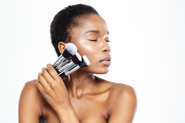 Entspannte afroamerikanische frau mit geschlossenen augen, die make-up-pinsel auf weißem hintergrund hält holding