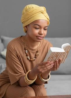 Entspannte arabische frau, die zu hause ein buch liest