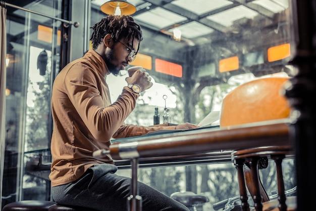 Entspannte atmosphäre. freundliche männliche person, die in halber position sitzt und nachrichten liest