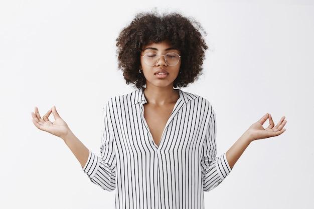 Entspannte attraktive moderne afroamerikanische weibliche geschäftsfrau, die lästigen lebensstil führt, der geduld im yoga sammelt, augen schließt, hände in zen-geste ausbreitend