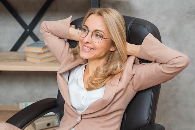 Entspannte blonde junge frau mit ihren händen hinter dem kopf, der auf stuhl sitzt