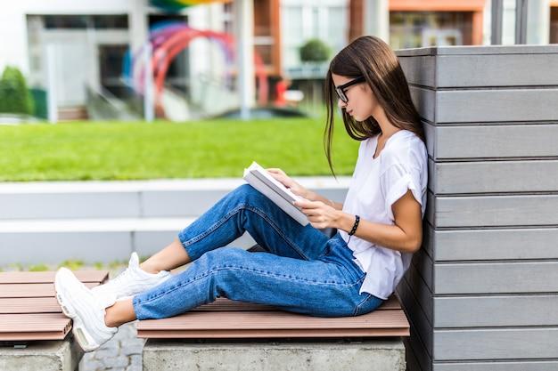 Entspannte frau, die ein festes buch bei sonnenuntergang liest, das auf einer bank sitzt