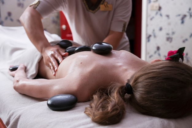 Entspannte frau, die eine massage mit heißen steinen bekommen