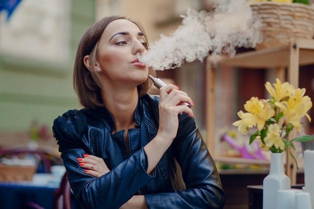 Entspannte frau, die elektronische zigarette raucht