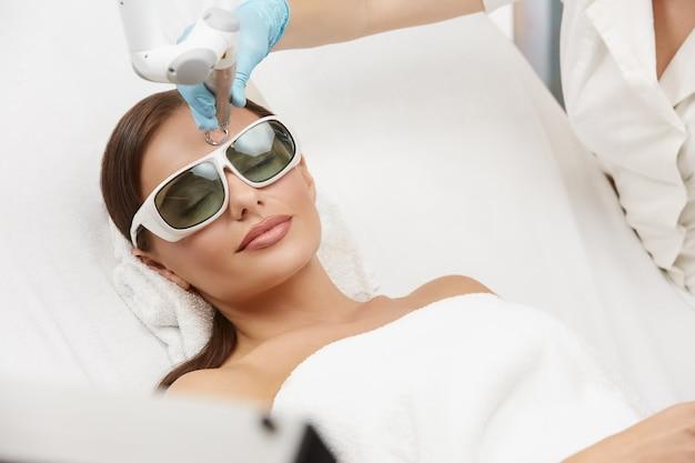 Entspannte frau, die laserverfahren im schönheitssalon auf weißem bett empfängt, frau, die gesichtsbehandlung im luxus-spa erhält