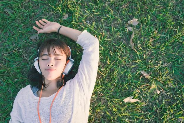 Entspannte frau, die musik mit den kopfhörern liegen auf dem gras hört