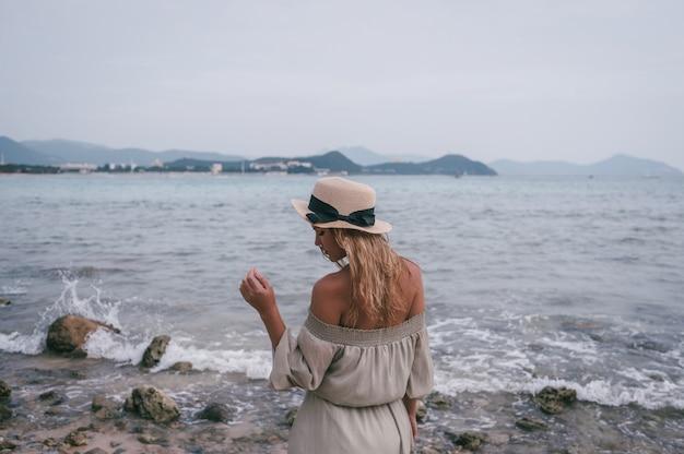 Entspannte frau, die ozeanbucht, -freiheit und -leben an der schönen strandküstenlinie im windigen wolkigen wetter genießt. junge dame, die sich frei, entspannt und glücklich fühlt. konzept von ferien, freiheit, glück, genuss