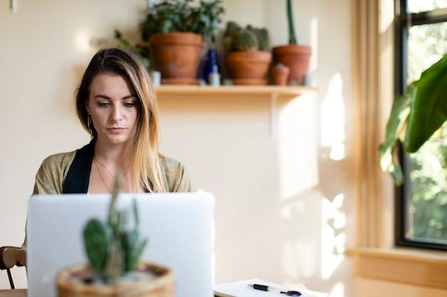 Entspannte frau, die von zu hause aus an ihrem laptop arbeitet