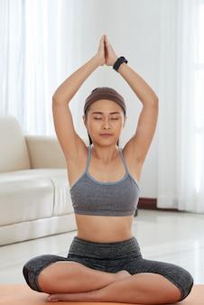 Entspannte frau, die zu hause meditiert