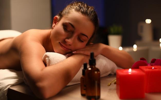 Entspannte frau liegt im spa-center im dunklen raum bei kerzenschein