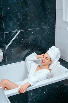 Entspannte frau mit handtuch auf haar in der badewanne liegend
