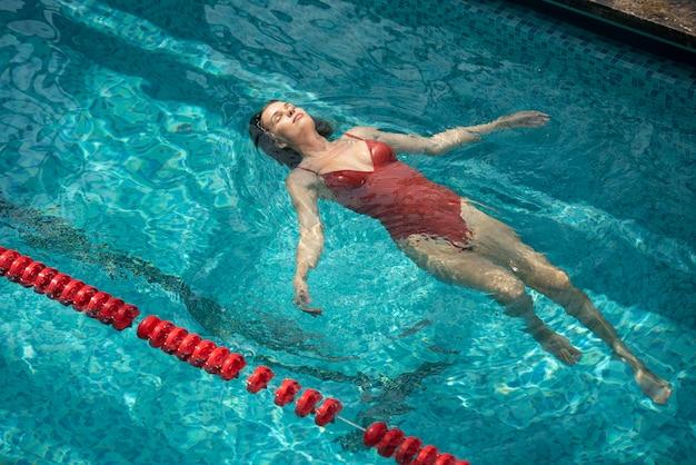 Entspannte frau mit mittlerem schuss im pool