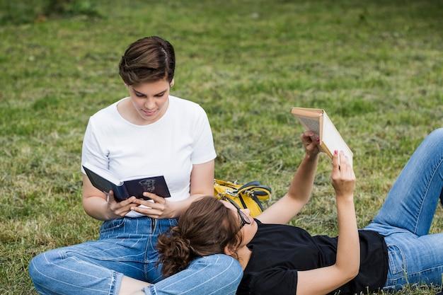 Entspannte freundinnen, die auf gras lesen