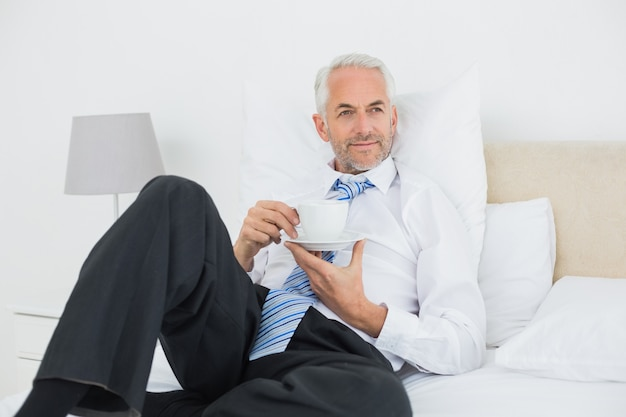 Entspannte geschäftsmann mit einer tasse tee im bett